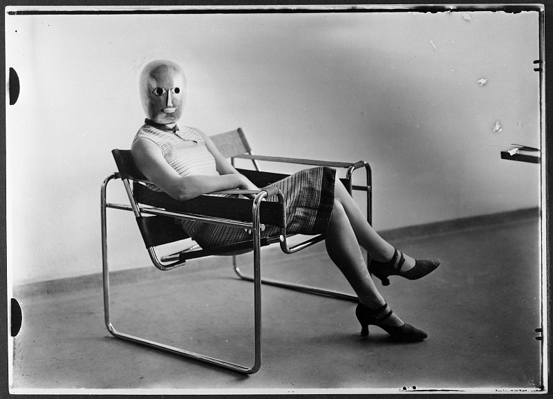 A woman wearing a mask by Oskar Schlemmer, seated in a Marcel Breuer Wassily chair